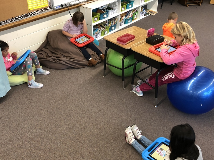 First graders using flexible seating and working on a math game.