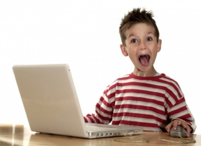 excited child next to computer